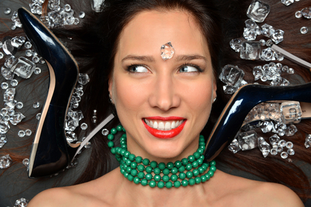 Beauty Fashion Glamour Girl Portrait. portrait of a luxurious brunette girl lies in a placer of diamonds jewelry, green beads and luxury accessories Stok Fotoğraf