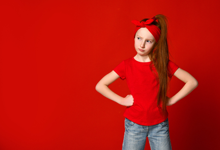 Cute little red-haired girl sulking and frowning while holding hands on the waist, offended and disappointed, standing over a red background.