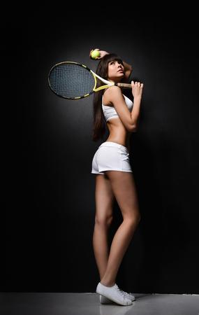 Portrait of a girl tennis player tennis racket in white uniform clothes on a dark background. Studio shot.
