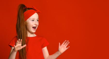little red-haired girl with a bandage on her hair in a red t-shirt happily shouts when she sees something to the side.