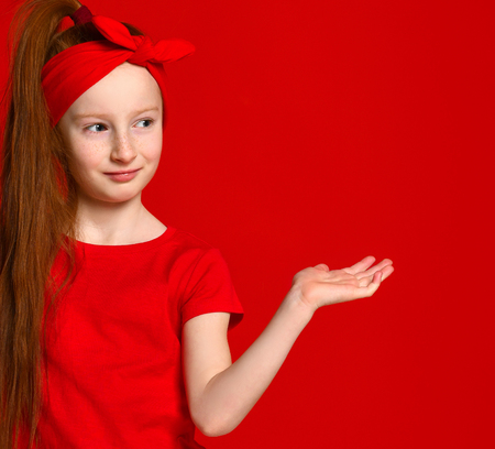 cute little red-haired girl with a bandage on her hair, smiles and places a spot for your advertisement. On a red background.