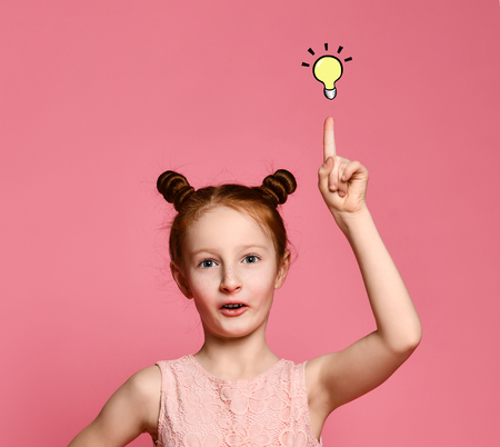 Happy girl redhead in pink dress posing with hand on hip while having an idea - a light is on and looking at camera over pink background Reklamní fotografie