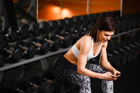 Chica deportiva descansando después de una dura sesión de entrenamiento en el gimnasio, sentada cerca del estante con pesas, escuchando música desde un teléfono móvil.
