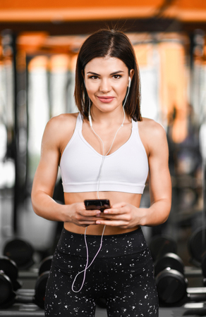 Sports girl resting after a hard workout and listening to music from a mobile phone. Stock Photo