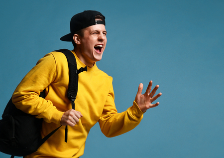 Joyful young man student with a backpack runs isolated in studio on a purple background. Stock Photo