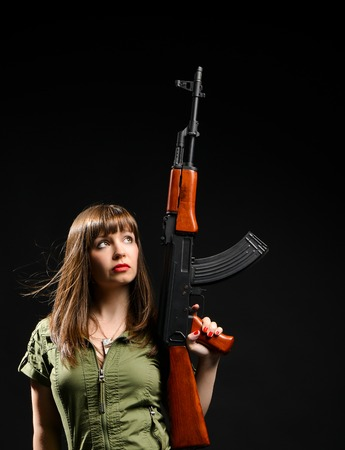 young brunette girl in a green khaki dress holding a gun on a black studio background.