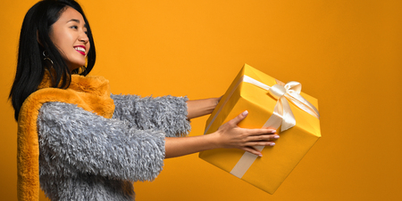Portrait of a cute Asian girl gives a gift box with joy isolated over a yellow background.