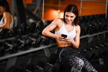 Sports girl resting after a hard training session in gym, sitting near the rack with dumbbells, listening to music from a mobile phone. Stock Photo