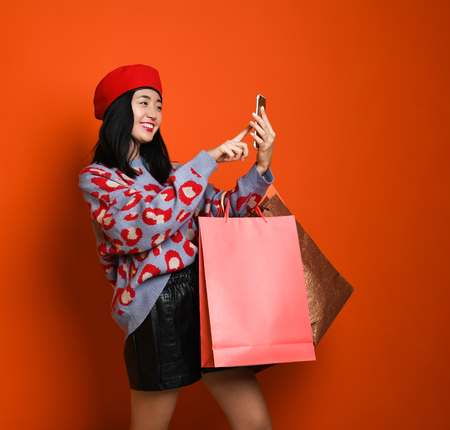 Beautiful young happy Asian woman in a stylish beret and sweater, with a colorful shopping bag using tablet for shopping online. shopping concept. Фото со стока