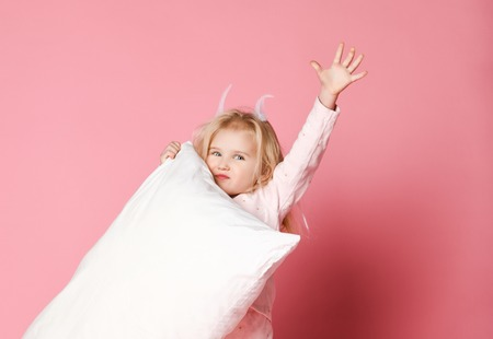 little girl blonde with feathers in her hair and pajamas holding a pillow in her hands and having fun at a pajama party. Sleepwear advertising Stock fotó