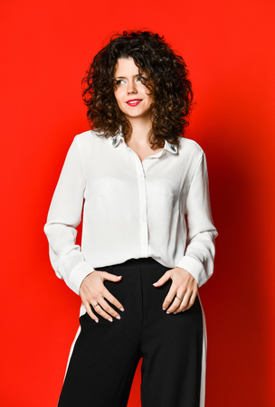 Fashionable and beautiful brunette model with curly hair in a white blouse and full-length pants posing in the studio, on a red background