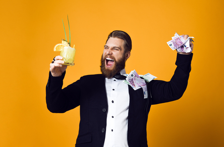 I am rich! Happy young businessman with glass of cocktail in formal clothes holding bunch of money banknotes and celebrating throwing money up