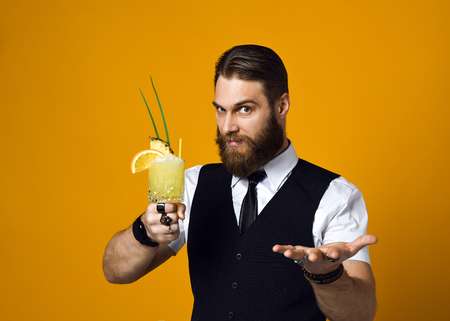handsome bearded barman with a long beard and mustache has stylish hair offers to treat himself and try a cocktail of his cooking, he is wearing a classic vest on a yellow studio background Standard-Bild
