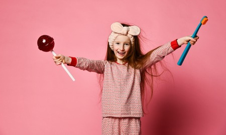 Little cute red-haired girl in pajamas holding in her hands a sweeping brush and lollipop. healthy teeth. Teeth protection from sweethearts