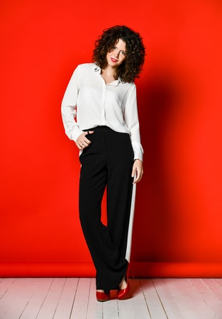 Fashionable and beautiful brunette model with curly hair in a white blouse and full-length trousers in red high heel shoes posing in the studio, on a red background