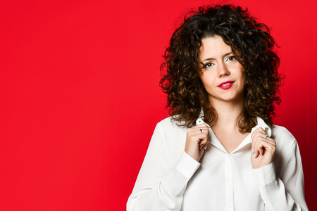 Fashionable and beautiful brunette model with curly hair in a white blouse posing in the studio, on a red background Stock Photo