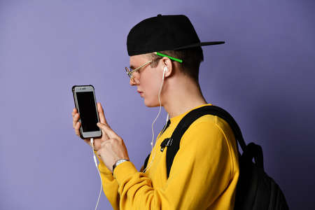 Portrait of a young student in a yellow sweater listening to music on headphones and holding a mobile phone, showing a screen. isolated on purple background