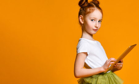 Cute red-haired girl school girl holding a tablet and looks into it. Side view. Child playing game, surfing or watching cartoon