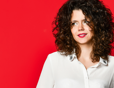 Fashionable and beautiful brunette model with curly hair in a white blouse  posing in the studio, on a red background