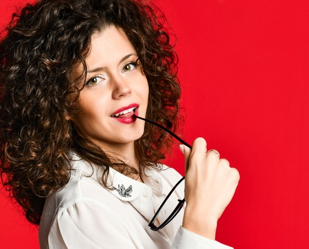 Closeup photo picture of lovely smart intelligent curly attractive lady looking at camera, wearing white shirt blouse, holding glasses in her hands isolated red background