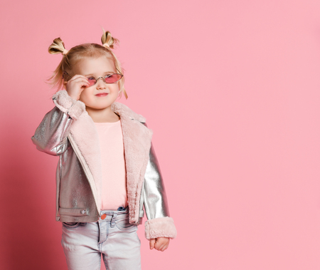 Portrait of a little girl in stylish clothing posing on pink background and playing up, cute emotional girl in girlish sunglasses
