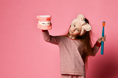 Red-haired pretty girl in pajamas with a toothbrush and a kissuos mock-up with scales stand over a pink background wall and the joy of a smile on camera.