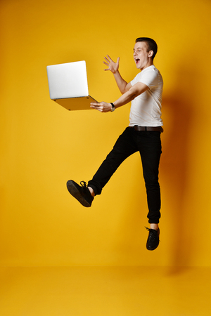 Full length of a smiling young student working, isolated on yellow background, working on a laptop, late for classes