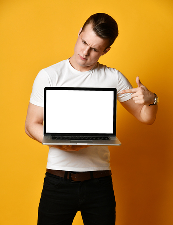 Photo Young Man 20s in a white t-shirt, holding and using a laptop turned blank white screen in the camera, standing isolated on a yellow background in the studio