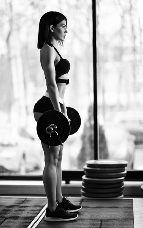 Fit beautiful girl doing squats with barbell in gym Stock Photo