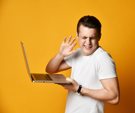 young man of the 20s in a white T-shirt, holding and using a laptop, clung to the screen - attentively looking at the screen. worried