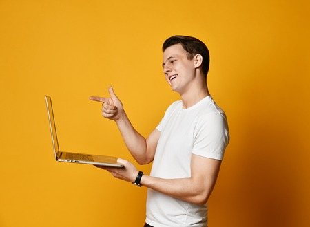 20s young man in a white T-shirt, holding and using a laptop, communicates online with someone over the Internet 版權商用圖片