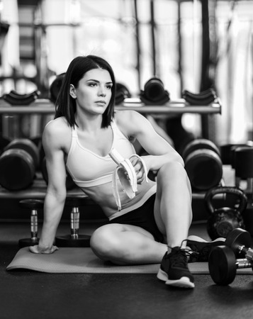 Young sporty woman has a break in training in the gym. makes a snack banana. Lifestyles and Healthcare theme Stock Photo