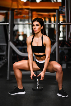 sexy young fitness woman doing squatting with heavy dumbbells in the sport club hall. Photo in dark and orange tones