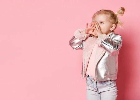 Portrait of a little girl in stylish clothing sitting on pink background and playing up Stock Photo