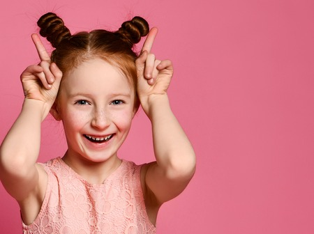 Smiling young crazzy red hair kid girl having fun and making horns by her hands, looking at the camera