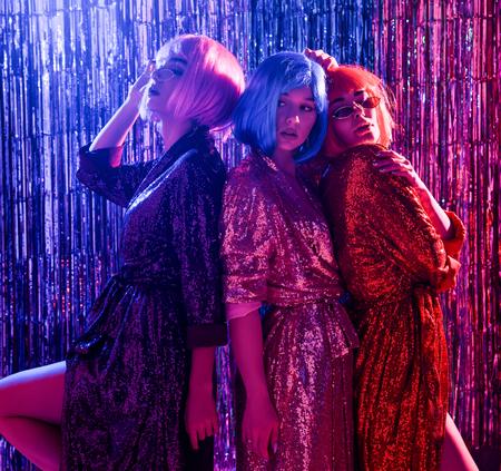 Trois amies en perruques et robes glamour stylées à sequins, sous les néons d'une discothèque. Célébrez, amusez-vous, célébrez quelque chose. Banque d'images