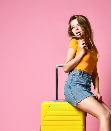 Traveler tourist woman in summer casual clothes with travel suitcase isolated on pink background. Travel concept. Copy space