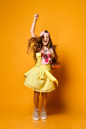 Charming fashionable teenager girl in skirt and sneakers joyfully jumping over yellow studio background Stockfoto