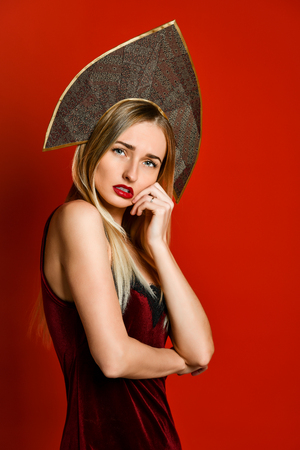 Beautiful blonde Russian girl in traditional kokoshnik hat, velvet festive dress on a red background, looking at th camera Stock fotó