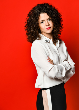 Beautiful curly brunette girl in a white blouse and black pants on a red background, posing in the studio. Stock Photo