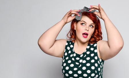 schönes Stilporträt einer vollfetten Frau plus Größe in einem Retro-Kleid und Make-up, einem Polka-Dot-Kleid, zieht ein stilvolles Retro-Haarband an. Pin-up-Mädchen Jahrgang. Standard-Bild