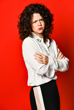 Angry Beautiful curly brunette girl in a white blouse and black pants on a red background, posing in the studio.