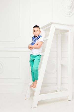 Fashion beautiful little boy in bright trousers and t-shirt and scarf over white background, stands climbing on the step of the stairs in the studio. Fashionable children