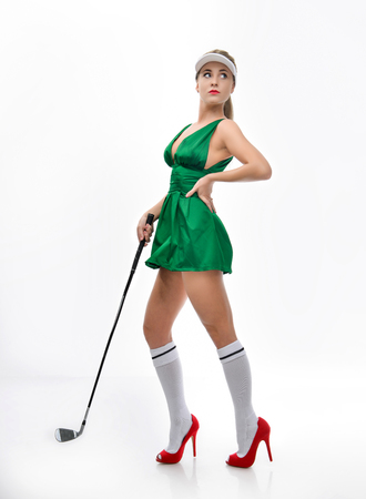beautiful girl the blonde in a short sexy green dress, in red shoes on a hairpin and white knee-highs holds a golf club. isolated on white background with space for your advertisement