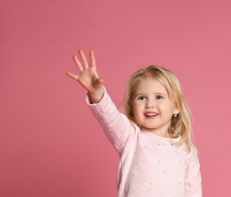 Little cute baby girl blonde in a pink suit pulls her hand forward something shows on a pink background.