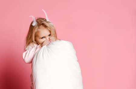 little girl blonde with feathers in her hair and pajamas holding a pillow in her hands and having fun at a pajama party. Sleepwear advertising