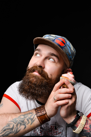 Happy bearded bald man holding a cream cake with anticipation of the pleasure of eating. on a black background. Banco de Imagens