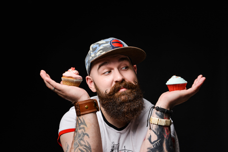 happy bearded man in a trendy stylish cap is holding two cream muffin cakes on a cobbler, making a choice of which one to eat. on a black background.