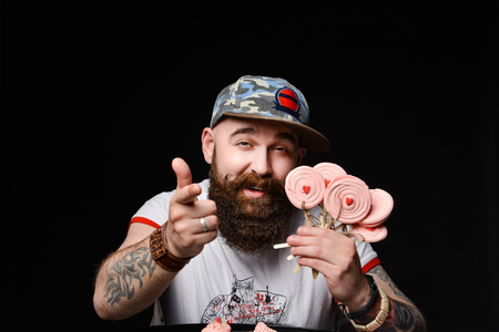 Happy bearded brutal man in a fashionable cap holds a pack of lollipops candies, isolated on a black background.
