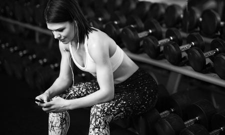 Sports girl resting after a hard training session in gym, sitting near the rack with dumbbells, listening to music from a mobile phone. black and white